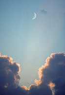Blue sky with clouds and crescent moon