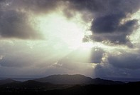 Sunrays shine through clouds as sun sinks behind mountains