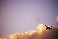 Airplane soars through blue sky and clouds at sunset
