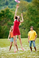 Young people playing with flying disc in meadow