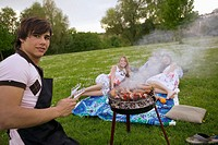 Young man grilling, young women in background