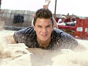 Young man throwing sand, blurred motion