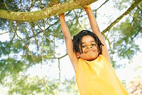 Young African boy hanging from tree branch