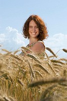 Young woman standing in cornfield, smiling