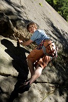 Young man rock climbing, looking down, low angle view