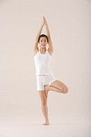 Young Asian woman in tree pose