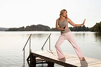 Woman exercising yoga on jetty