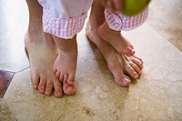 Close-up of mother and infant girl's barefeet. Infant is standing on mother's feet