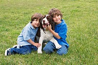 Two young boys pose with a dog on a grass lawn