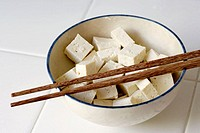 Pieces of Tofu cut into cubes and sitting in a bowl with a pair of chopsticks resting on top.