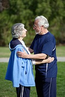 Active senior couple in exercise clothes embrace each other in an outdoor park