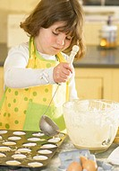 Girl (5-7) making cupcakes