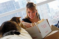 20 yr old woman home shopping on laptop computer looking at pet cat