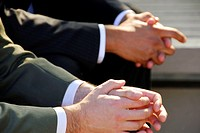 2 young male business men sitting outdoors with hands folded rested on knees