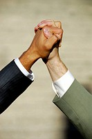 2 young male business men clasping hands together