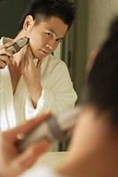 Man looking in mirror, shaving