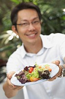 Man holding plate of salad to camera