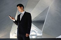 Businessman standing in tunnel, looking at mobile phone