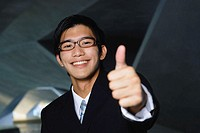 Businessman looking at camera, making a thumbs up sign