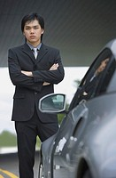 Businessman with arms crossed, standing next to car, portrait