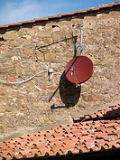 Satelite TV dishes contrast with older houses in Cortona, Italy