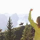 Woman waving at people horseback riding in mountains at sunset