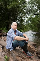 Man sitting on rocks near a stream