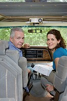 Couple planning trip with a map in caravan