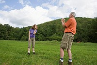 Woman posing for photographs in a field