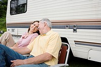 Mature couple sitting near a caravan