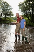 Mature couple fishing in stream
