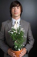 Young businessman holding a plant