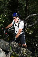 Mountain biker climbing up rocks