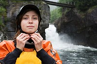 Female kayaker adjusting helmet