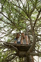 Young couple sitting on tree house, smiling, low angle view