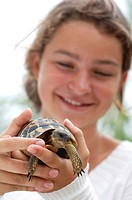 Girl holding turtle, close-up
