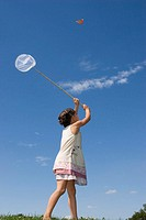 Girl (7-9) holding net, trying to catch butterfly