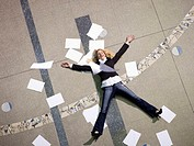 Woman lying on floo surrounded by papers