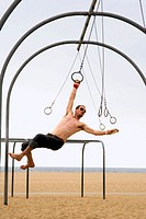 Caucasian man on the rings set, swinging from one ring to the next. Santa Monica Beach, Los Angeles, California.