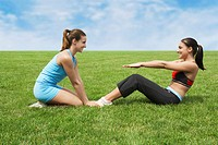 Two young women doing sit-ups on grass, sister assisting