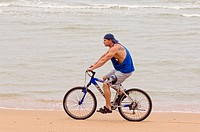 Young Caucasian musle man on beach with mountain bike. Jomtien Beach. Pattaya. Thailand
