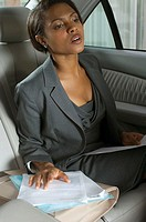 Businesswoman straining to see from backseat