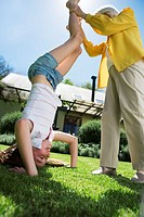 Woman Helping Granddaughter Attempt a Handstand