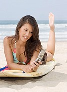 Young Woman Lying on Surfboard and Using Cell Phone