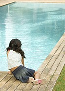 Little girl sitting by edge of swimming pool, rear view