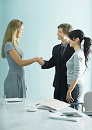 Businessman and woman shaking hands while casually dressed young woman stands by