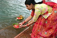 A Rajasthani women doing an offering alongside the sacred river Ganges in Haridwar, a sacred place in India. Haridwar is located in Uttaranchal, at th...