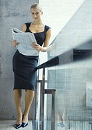 Businesswoman leaning against glass guard rail, reading newspaper, full length