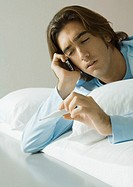 Man lying in bed, using cell phone and holding up thermometer