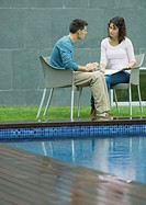 Man and woman talking by poolside